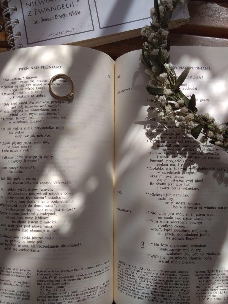 Pismo święte z pierścionkiem zaręczynowym, otwarte na Pieśni nad Pieśniami