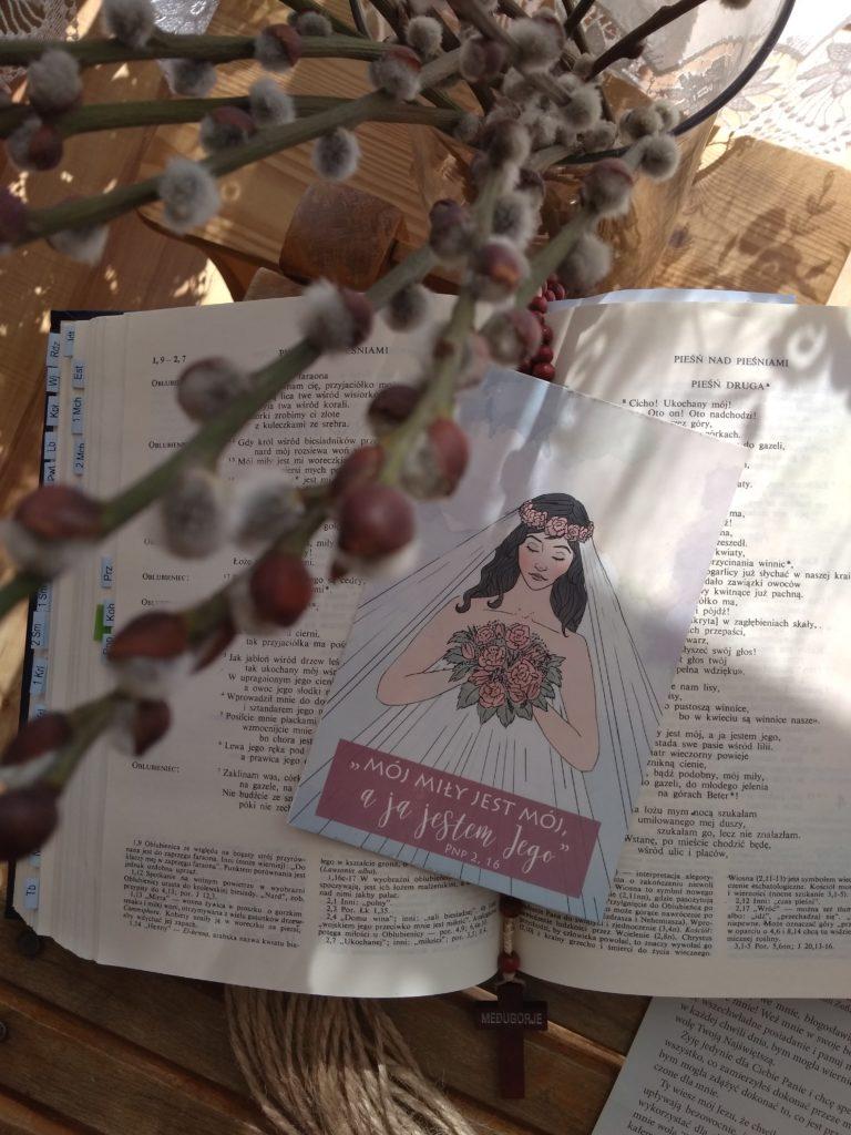 """pocztówka ułożona na Piśmie św., przedstawiająca Oblubienicę, obok cytat z Pieśni nad Pieśniami - """"Mój miły jest mój, a ja jestem jego""""."""