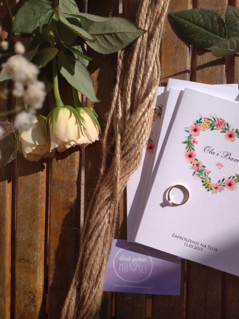 Zaproszenia ślubne z pierścionkiem zaręczynowym. Zdjęcie ma nawiązywać do spisywania protokołu przedślubnego, który jest jednym z elementów przygotowań do sakramentu małżeństwa.